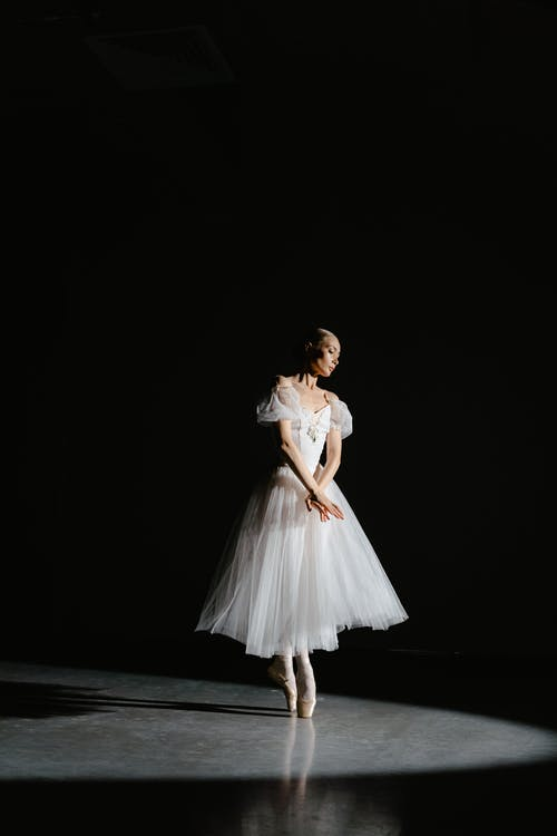 Woman in White Dress Standing on Black Floor