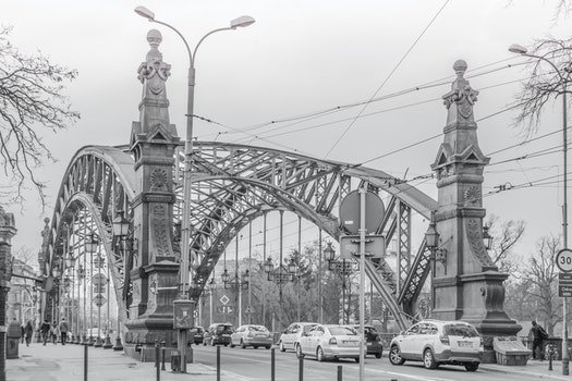 Greyscale Photo of a Bridge With Cars Being Caught in a Traffic during a Snow Weather