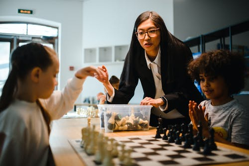 Woman Standing Next to Children Playing Chess