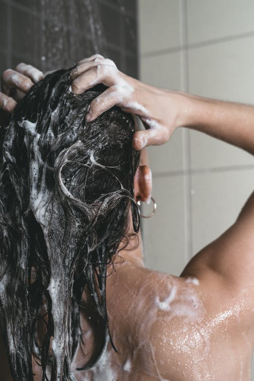 Close-Up Photo of a Person Washing Her Hair