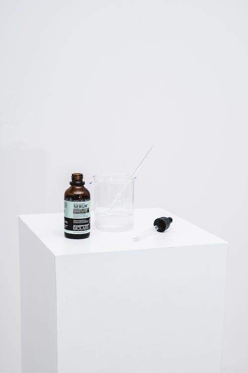 Brand Logo Serum Bottle and Beaker on White Tabletop