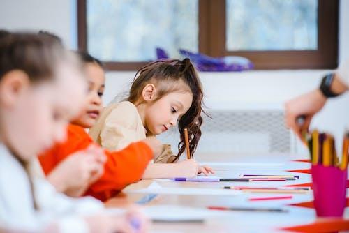Girl in Orange Long Sleeve Shirt Holding Pen Writing on White Paper