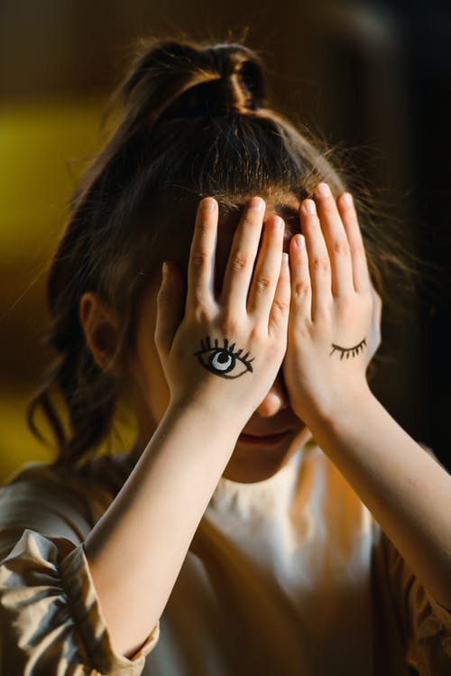 Woman in White Shirt Covering Face With Her Hands