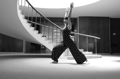 Woman in Black and White Polka Dots Jumpsuit Doing Yoga Pose