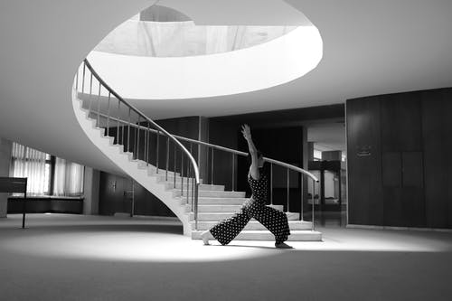 Grayscale of a Woman in Polka Dots Jumpsuit Doing Yoga Pose Beside the Staircase