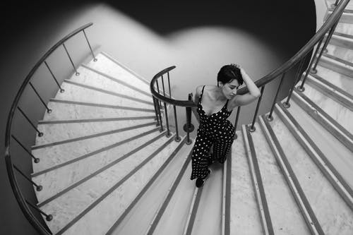 Woman in Black and White Polka Dots Jumpsuit Standing on Staircase