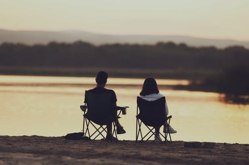 Man and Woman Sitting on Chair on Sand during Sunset
