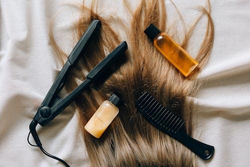 Black Hair Comb Beside White Plastic Bottle