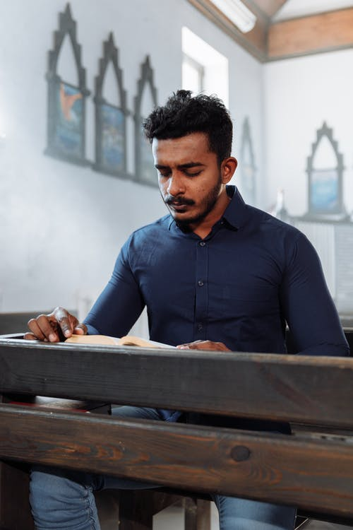 Man in Blue Shirt Sitting on Wooden Bench in Church and Reading