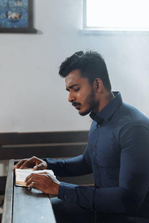 Man in Dark Blue Shirt Reading Bible