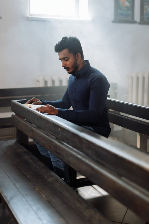Man in Blue Dress Shirt Sitting on Bench and Reading