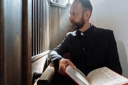 Priest in Black Dress Shirt Holding Bible