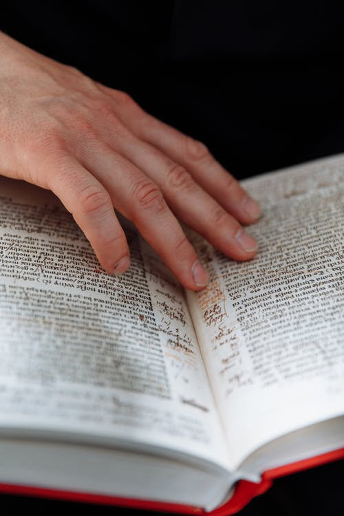 Persons Hand on Book Page