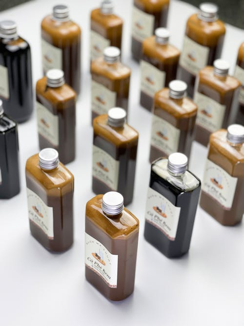 From above collection of glass bottles filled with tasty sweet syrups for coffee placed on white table in light room