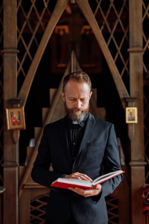 Man in Black Suit Reading Book