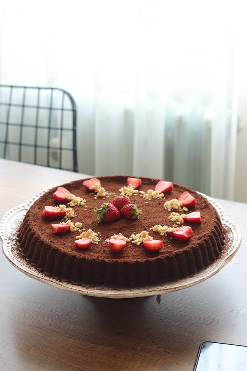Chocolate Cake with Strawberries on Top on Wooden Table