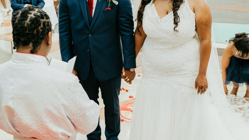 Crop anonymous bride and groom in elegant wedding outfits holding hands while standing on street with guests during festive ceremony