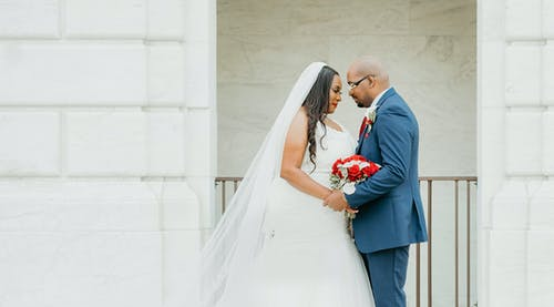 Side view of African American groom and bride holding hands while standing near white building on street during wedding celebration