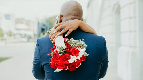 Back view of anonymous groom embracing unrecognizable bride with bouquet of flowers while standing on street with buildings in city
