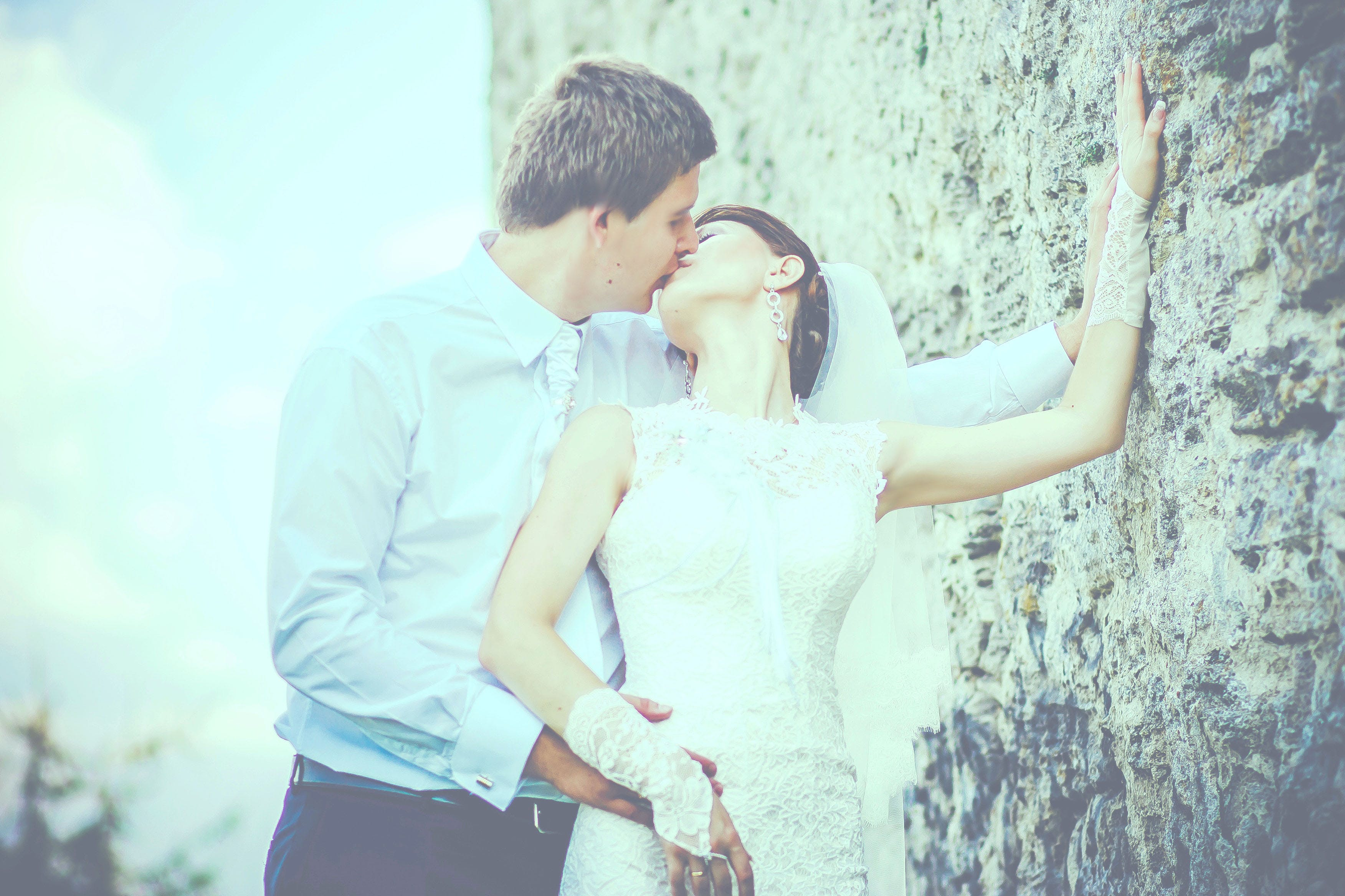 Man Kissing Woman Wearing Sleeveless Wedding Gown