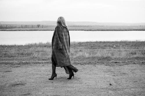 Woman Wearing Trench Coat Walking on Lakeshore