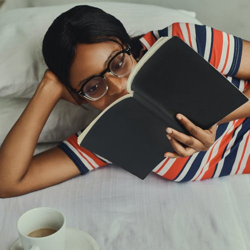 Woman in Striped Shirt Reading a Book