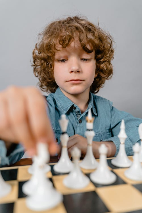 Close-Up Photo of a Smart Boy Playing Chess