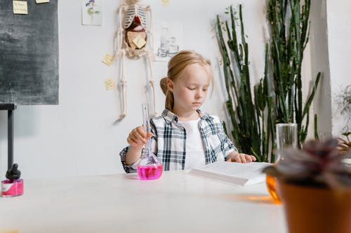 A Smart Girl Reading a Book while Doing a Science Experiment