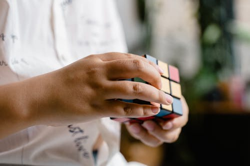 Close-Up Photo of a Child Solving a Rubik's Cube