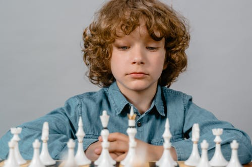 Close-Up Photo of a Serious Boy Looking at the White Chess Pieces