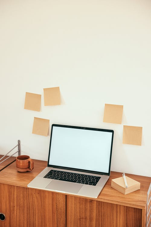 Laptop and Sticky Notes on Wooden Work Desk