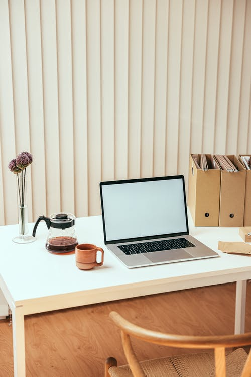 A Macbook on White Table