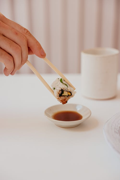 Close-Up Photo of a Person Dipping a Delicious Sushi Roll on a Soy Sauce