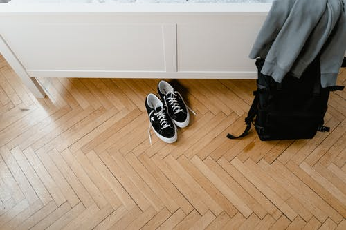 High-Angle Shot of a Black Sneakers and Backpack on Wooden Flooring