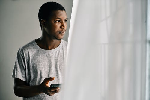 Man in Gray Crew Neck Shirt Holding White Curtain