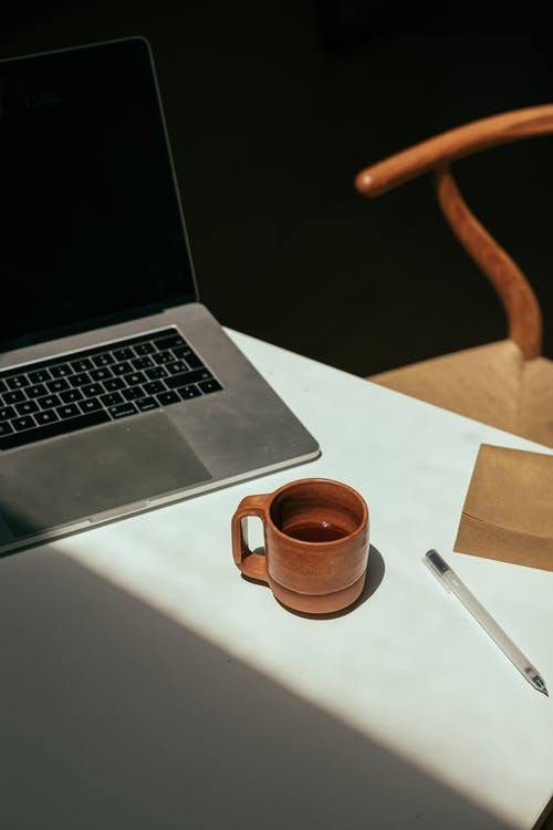 A Cup of Coffee beside the Laptop and Sign Pen