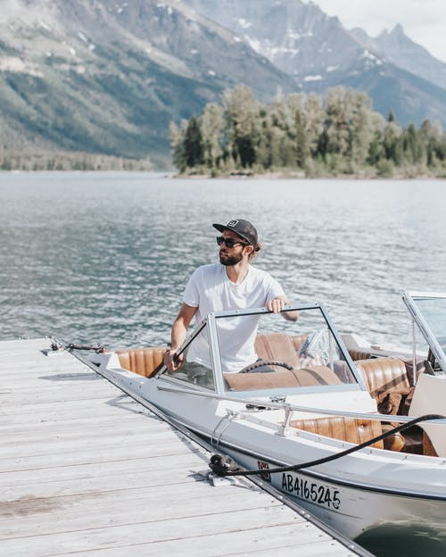 Man in White Polo Shirt Sitting on White Boat