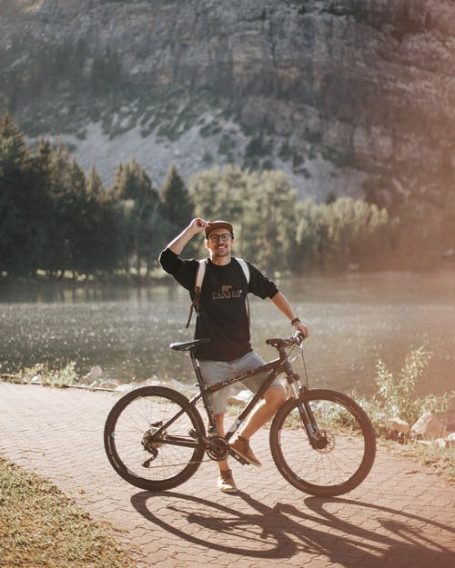 Woman in Black Long Sleeve Shirt Riding on Black Mountain Bike Near Body of Water during