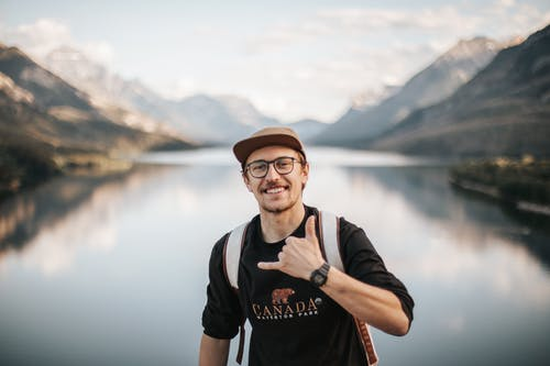 Man in Black Crew Neck T-shirt and Brown Hat Standing Near Lake