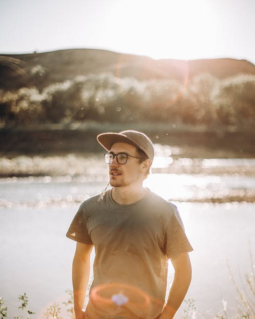 Man in Brown Crew Neck T-shirt and Black Hat Standing on Water