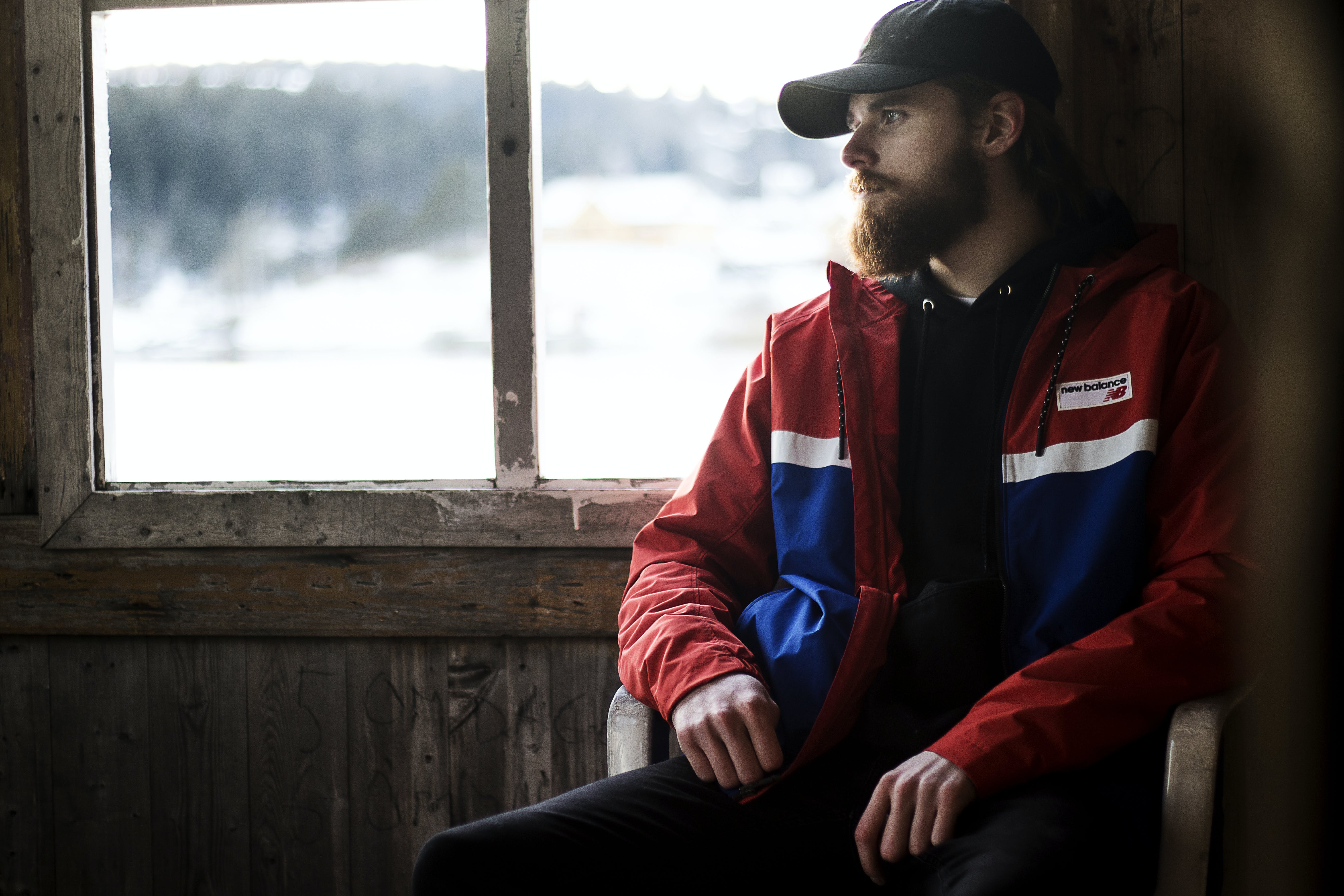 Photo of Man Wearing Black Hat and Blue-and-red Jacket Near Window