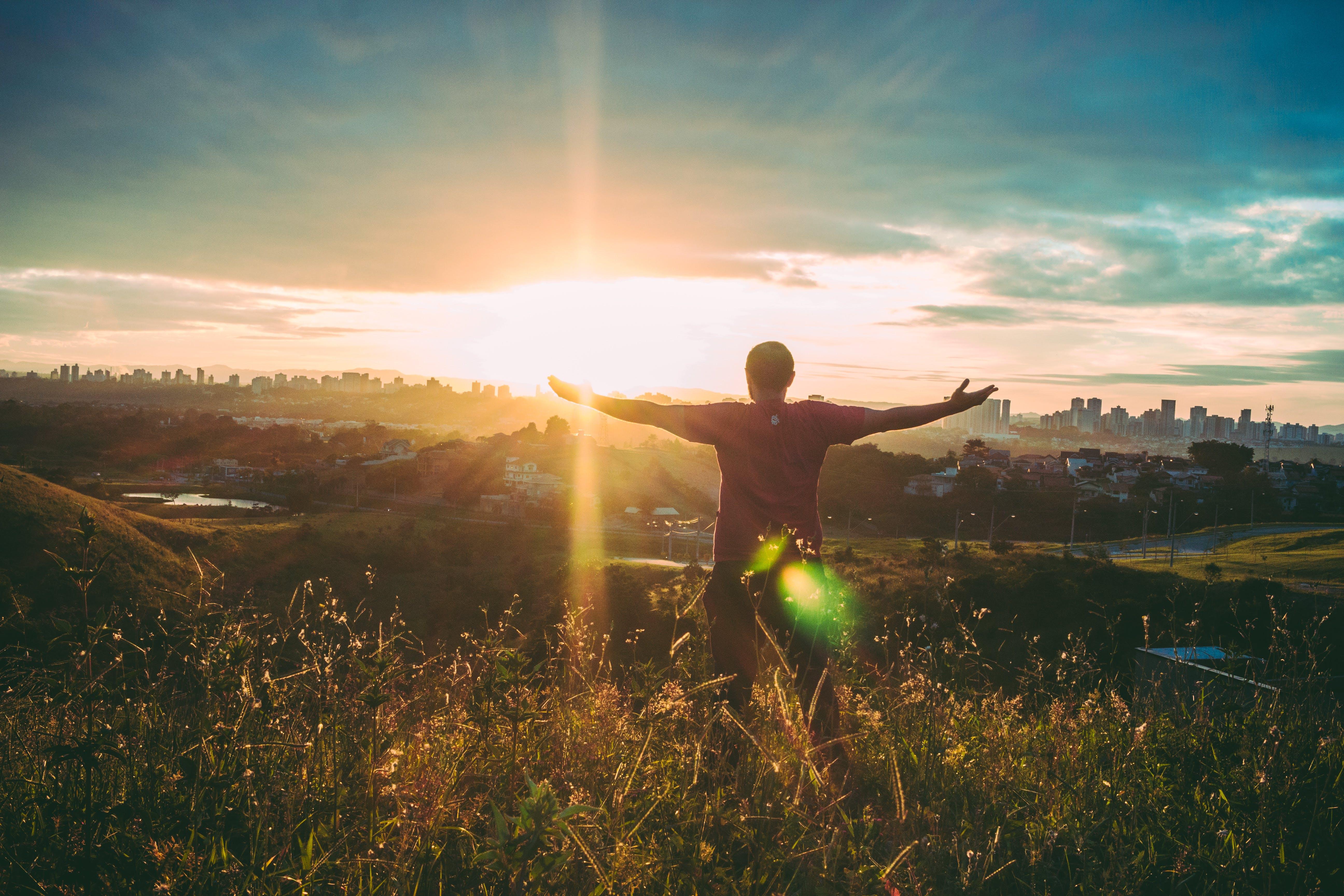 Foto profissional grátis de ajuda quando quer, alvorecer, braços abertos, brilho do sol