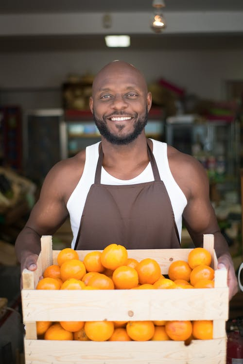 A Man Carrying a Crate with Fresh Oranges