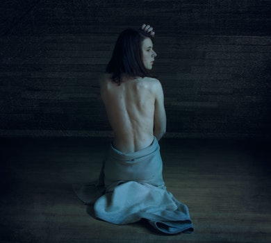 Woman Wearing Gray Skirt Sitting on Brown Wooden Floor