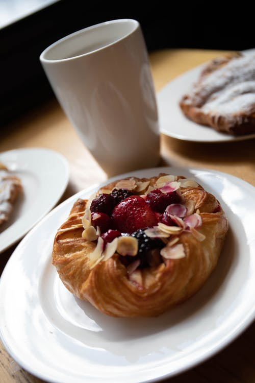 Pastry With Red Strawberry on Top Near a Ceramic Mug