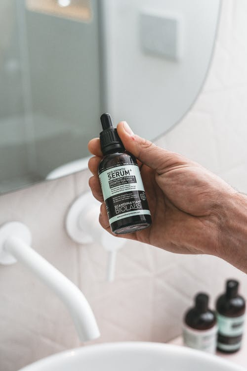 Hand Holding A Bottle Of Serum