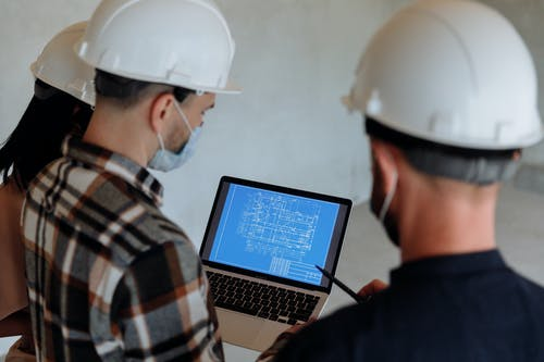 People in Hard Hats Looking at a Blueprint on a Laptop