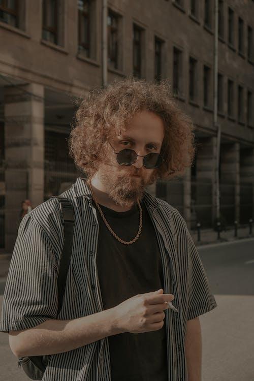 Man in Striped Polo Holding a Cigarette