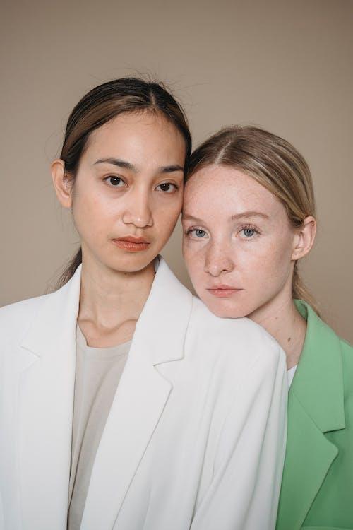 Women in White Blazer Standing beside Woman in Green Blazer