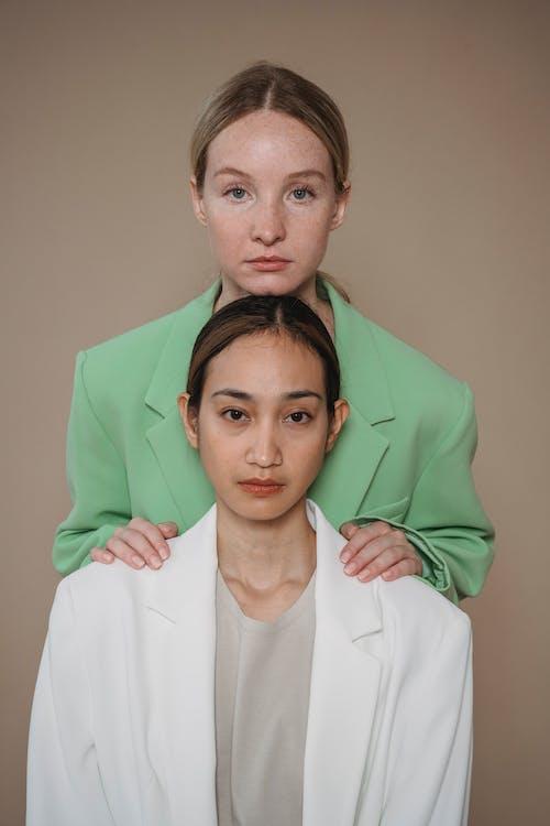 Woman in Green Blazer Standing behind Woman in White Blazer